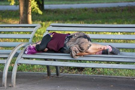 Homeless elderly woman sleeps on bench in Park