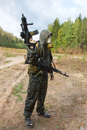 bullet proof: A soldier stands alone wearing state of the art bullet proof body armor, camouflage, and gas mask, holding an automatic weapon. Stock Photo