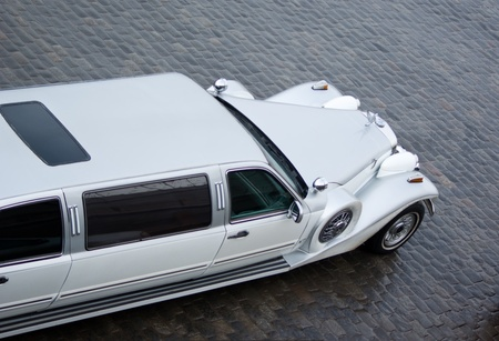 Part of Limousin Excalibur Phantom in outdoor. White car for wedding ceremony on quay at the river of Moscow. In rainy weather