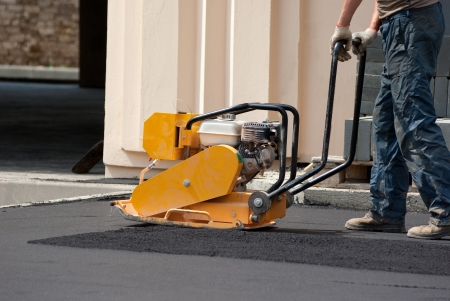 compactor: Man work with Vibratory plate compactor roll asphalt