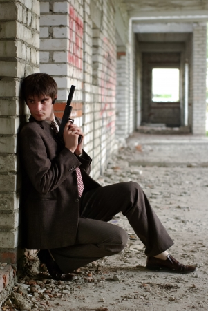 Young agent in suit with gun in skirmish