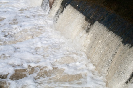 reproaching water, pouring through dam photo