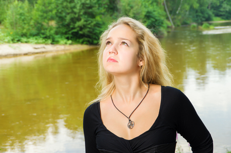 Woman looking in heaven against river photo
