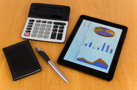 palmtop: Calculator, tablet computer with chart and graphs, notepad on table Stock Photo