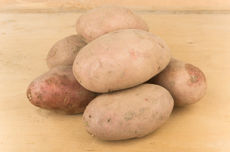 unwashed: Lavate patate crude che si trovano sulla superficie di legno