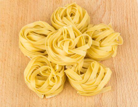 hardboard: Six pasta in form nest on wooden board