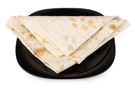 Folded triangle of thin Armenian lavash in black glass plate isolated on white background photo