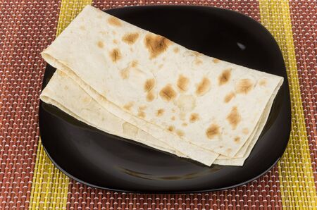Folded of thin Armenian lavash in black glass plate on bamboo mat photo
