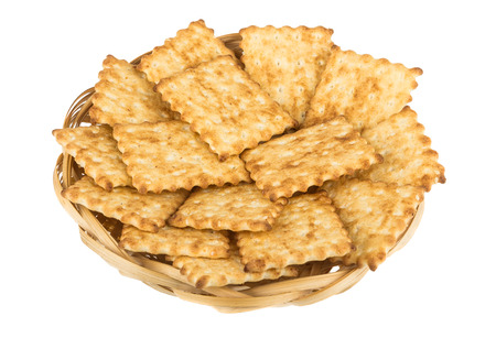 sesame cracker: Fresh cookies in woven wooden basket isolated on white background