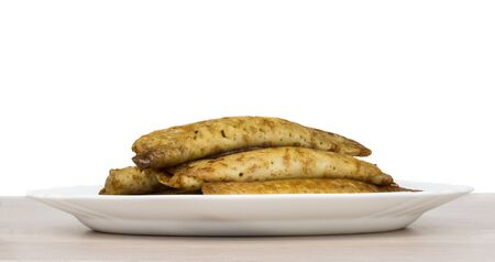 side dishes: Pancake stuffed in white dish on wooden table, side view