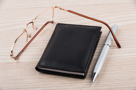 goldish: Notepad, pen and glasses on wooden table Stock Photo