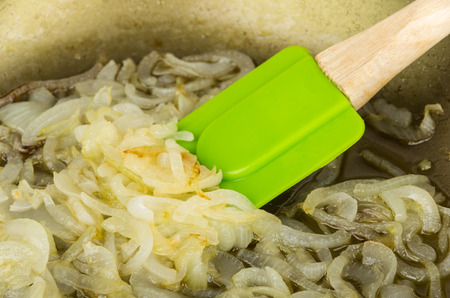 Close up of fried onions in pan and green spatula