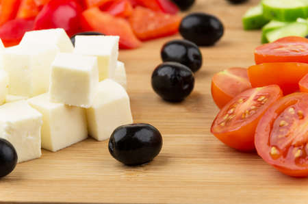 Slices of cheese tomatoes peppers cucumbers and black olives on wooden board photo