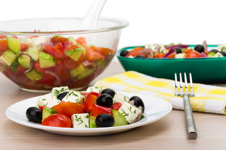 salad fork: Transparent glass bowl and plate with Greek salad fork napkin isolated on white background Stock Photo