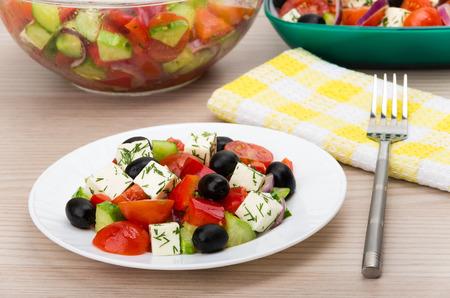 salad fork: Transparent glass bowl and plate with Greek salad fork napkin on wooden table