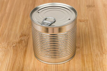 unlabelled: Closed metal cans with ring on wooden bamboo board