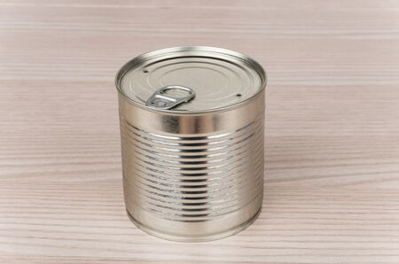 unlabelled: Closed metal cans with ring on wooden table