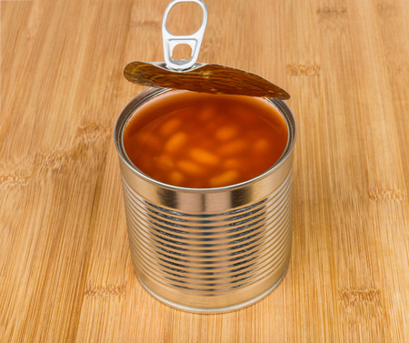 unlabelled: Open metal cans with beans in tomato sauce on bamboo board Stock Photo