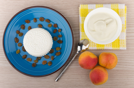 granular: Granular curd and raisins in blue plate sour cream and peaches  on table top view Stock Photo