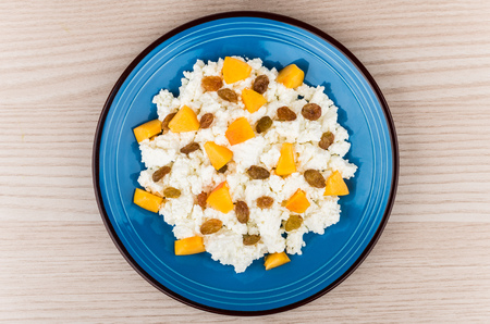 granular: Granular curd in blue glass plate mixed with peaches and raisins on wooden table top view Stock Photo
