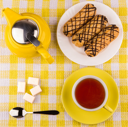 Hot tea in cup, sugar cubes and eclairs on yellow plaid tablecloth, top view Archivio Fotografico