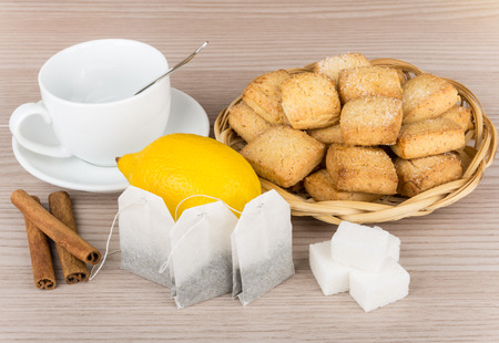 packets: Lumps of sugar, cinnamon sticks, lemon, packets of tea and cookies in wicker basket on wooden table