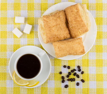 flaky: Black coffee, pieces of lemon and sugar, plate with flaky biscuits on yellow tablecloth, top view Stock Photo