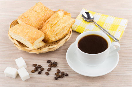 flaky: Hot black coffee, wicker basket with flaky biscuits, sugar cubes on wooden table Stock Photo