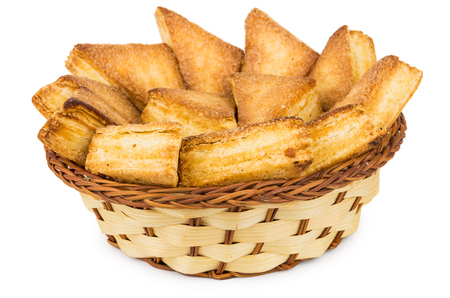 trigonal: Sweet puff pastries in wicker basket isolated on white background