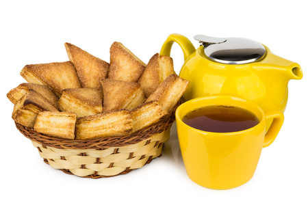 trigonal: Sweet puff pastries in wicker basket, teapot and hot tea in cup isolated on white background