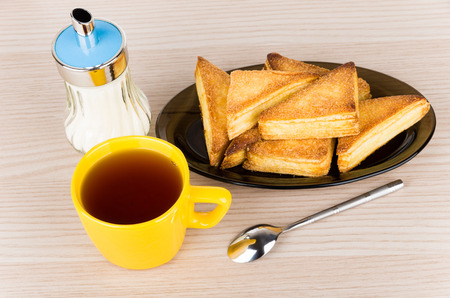 trigonal: Sweet puff pastries in glass dish, sugar bowl and hot tea in cup on table Stock Photo