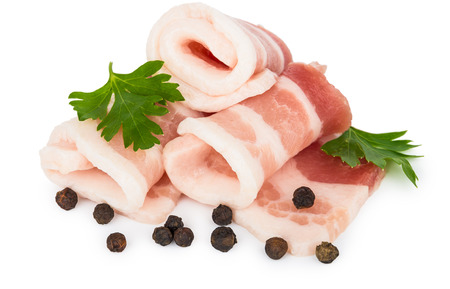 Heap of raw pieces of raw bacon with parsley and pepper isolated on white background