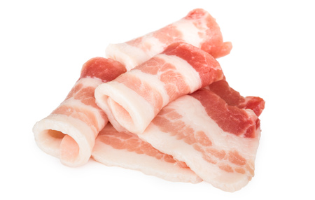 Heap of rolled pieces raw bacon isolated on white background Foto de archivo