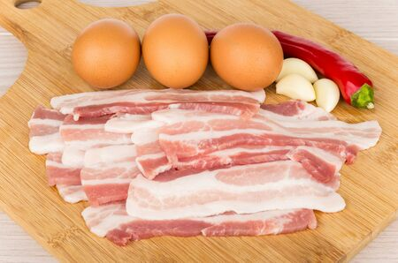 bacon and eggs: Pieces of raw bacon, eggs and chili peppers on wooden board on table Stock Photo