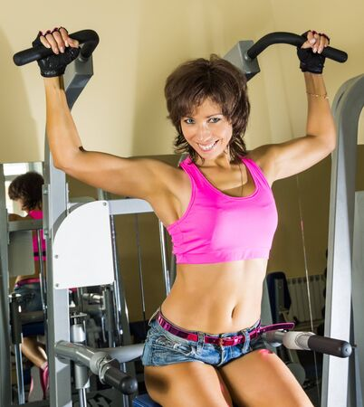 gym clothes: Playfully smiling young beautiful woman at gym
