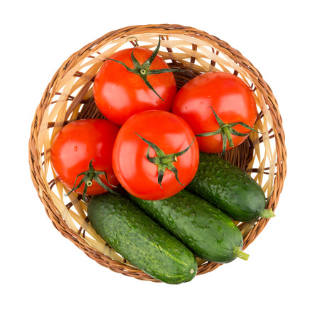 basket: Wicker basket with fresh tomatoes and cucumbers isolated on white background, top view Stock Photo