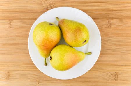 pera: Tres peras en plato blanco sobre la mesa de madera, vista desde arriba