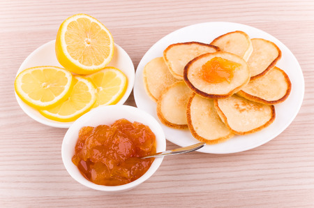 citrous: Homemade pancakes with peach jam and lemon on table