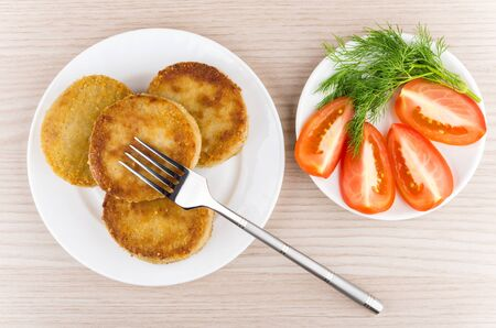 wooden table top view: Prepared cutlets in plate with dill and tomatoes on wooden table, top view
