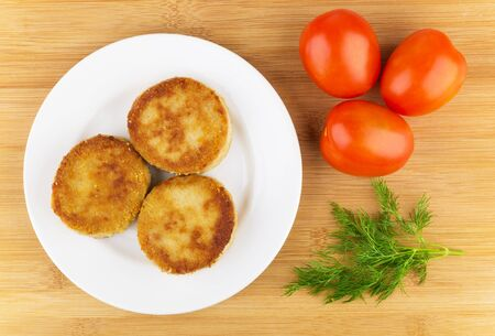 wooden table top view: Three fried cutlets in plate, red tomatoes and dill on wooden table, top view Stock Photo