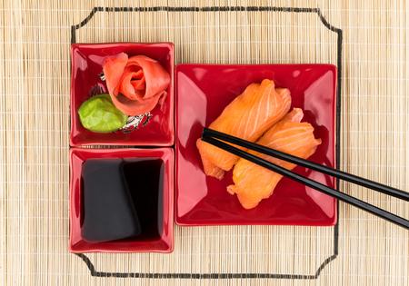 comida japonesa: Sushi con salmón, salsa de soja, jengibre, wasabi en la estera de bambú. Vista superior Foto de archivo