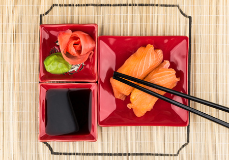 japanese food: Sushi with salmon, soy sauce, ginger, wasabi on bamboo mat. Top view