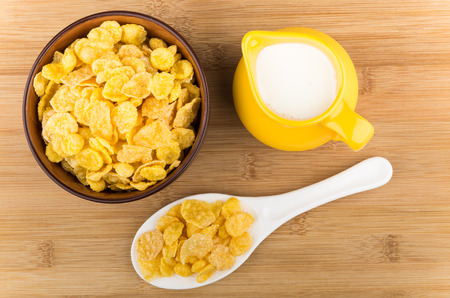 Bowl with corn flakes, jug of milk and plastic spoon on table, top view