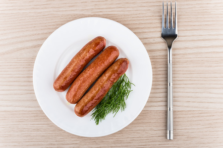 wooden table top view: Three fried sausages with dill in glass plate and fork on wooden table, top view Stock Photo