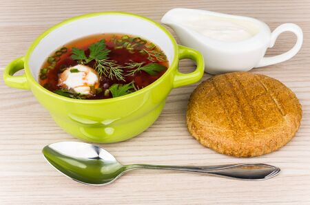 sour cream: Vegetable soup with beets, bread and sour cream on table