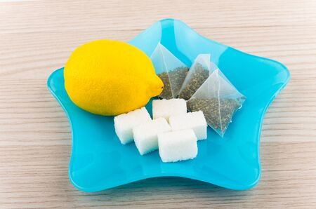 citrous: Lemon, sugar and tea bags in blue glass plate in shape of star on table Stock Photo