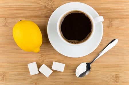 citrous: Hot cup of coffee, lemon, spoon and sugar on wooden table, top view Stock Photo