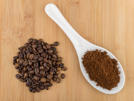 grinded: Ground coffee in plastic spoon and heap of coffee beans on wooden table