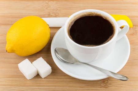 citrous: Hot cup of coffee, lemon, knife, spoon and sugar on wooden table Stock Photo