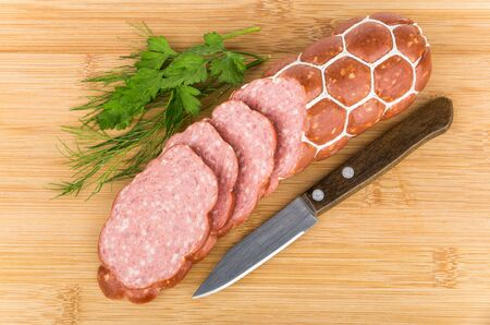 dill and parsley: Cut pieces of smoked sausage, dill, parsley and knife on wooden board Stock Photo